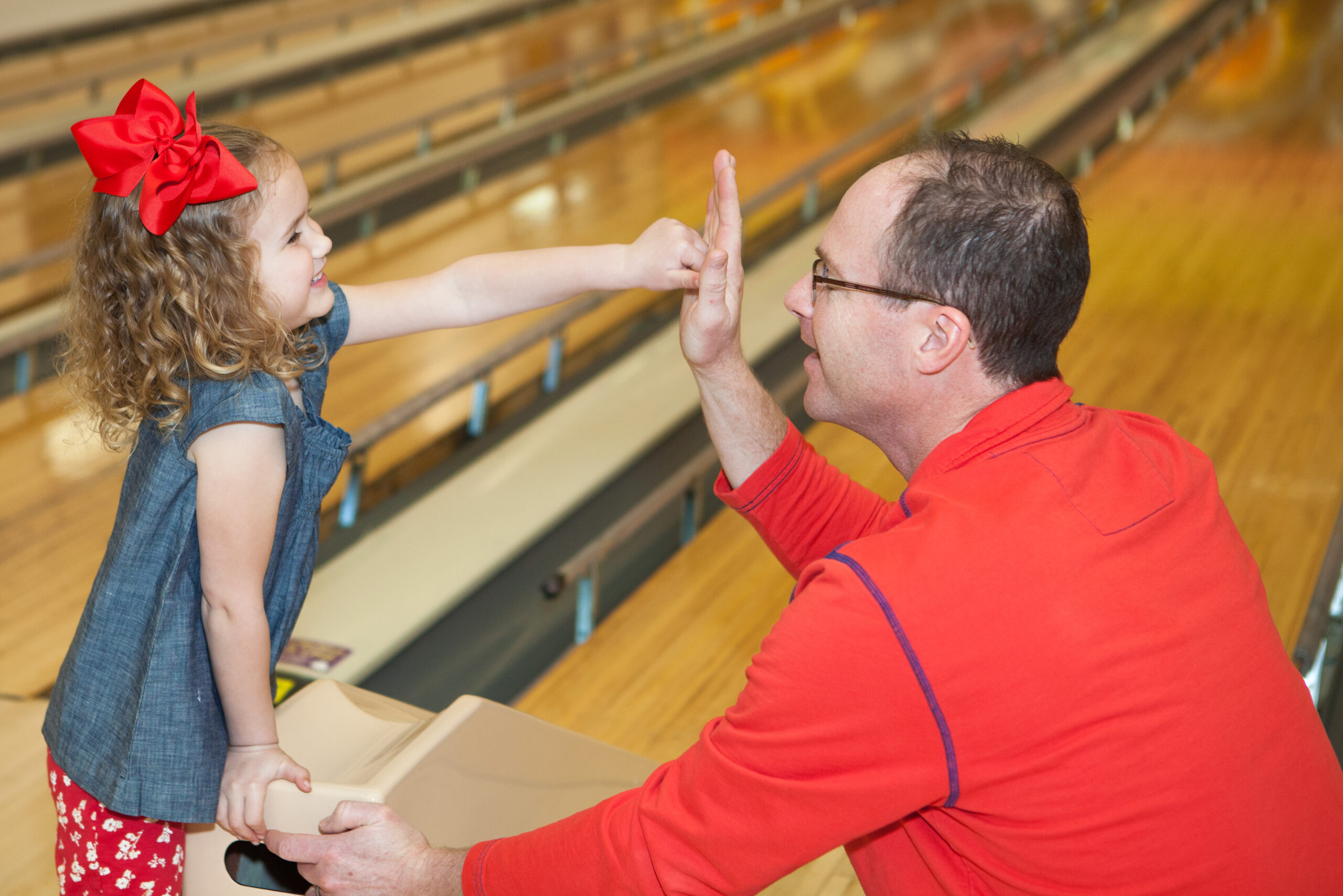 Little Girl giving dad a high 5 after bowling with a ramp and using bumpers